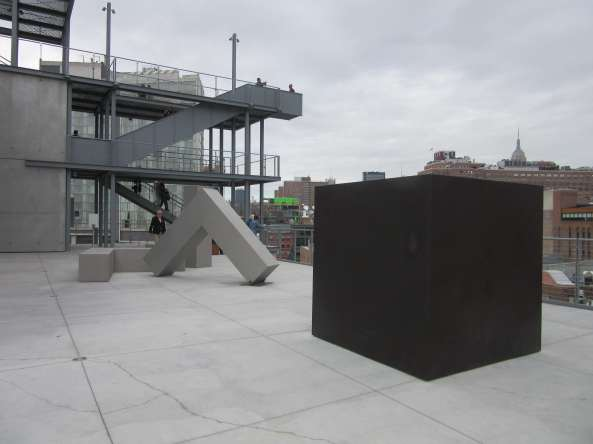 View of the sixth-floor Whitney terrace with Die by Tony Smith, 1962, steel, Whitney Museum of American Art, New York; Purchased with funds from the Louis and Bessie Adler Foundation, Inc., James Block, The Sondra and Charles Gilman, Jr. Foundation, Inc., Penny and Mike Winton, and the Painting and Sculpture Committee); and Robert Morris, untitled (4 Ls), 1965, (refabricated 1970), stainless steel, Whitney Museum of American Art, New York; Gift of Howard and Jean Lipman). Photo by Ken Carpenter.